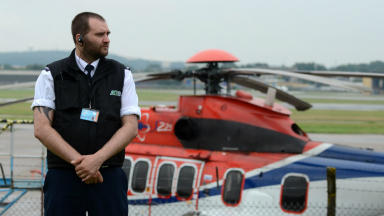 A security guard watches over CHC's grounded Super Puma helicopters at Aberdeen Airport.