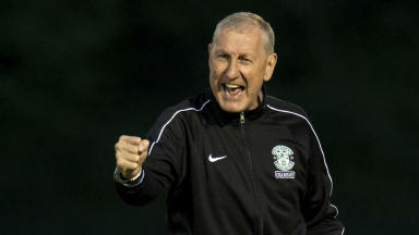 Elation: Hibs boss Terry Butcher celebrates on the New Douglas Park turf after the first leg victory.