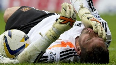 Grounded: Neil Alexander lies in pain on the Ibrox turf after fracturing his cheekbone in Hearts' 2-1 victory.