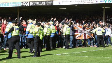 Motherwell fans congregate in front of Rangers supporters on the pitch after their play-off final win.