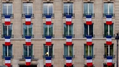 French flags hang from windows of a building in Paris