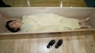 A South Korean woman takes part in her own mock funeral.