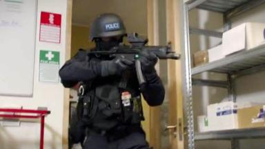 Video: Armed police raid building in advice video.