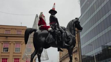Statue: Santa climbs on top of Duke of Wellington statue in Glasgow city centre.