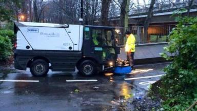 Council workers drain away the puddle to clear the path.