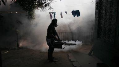 A man fumigates his neighbourhood in El Salvador