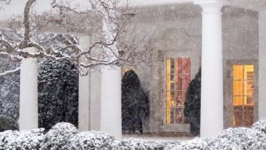 President Barack Obama is seen working through the window of the Oval office in Washington as the snow storm hits the capital.