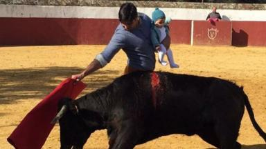 Francisco Rivera holds his baby daughter Carmen while fighting a bull.