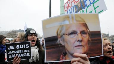 A woman holds a sign with Jacqueline Sauvage's face on it.
