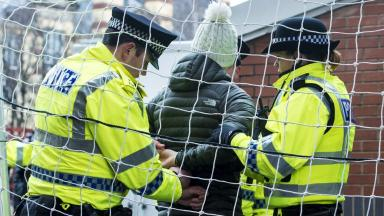 Police arrest a football fan at Hearts v Hibernian match in February 2016.