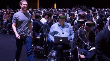 Mark Zuckerberg (right) walks past journalists wearing VR headsets.