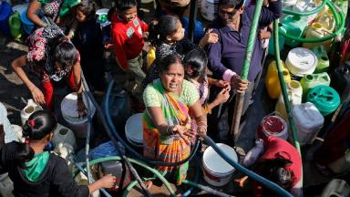 Residents fill their containers with water from a tanker in New Delhi.