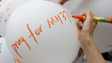 A relative of a passenger aboard missing Malaysia Airlines flight MH370 writes on a balloon at a remembrance event.