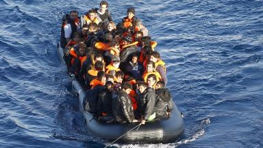 A dinghy full of refugees and migrants is towed by a Turkish Coast Guard