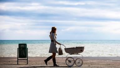 Women who have children before the age of 33 earn less, according to research