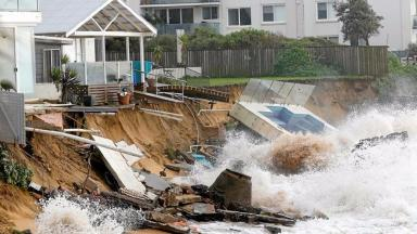 A wave crashes against a swimming pool and properties after they were damaged by severe weather at Collaroy beach in Sydney.