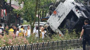 People stand beside beside a Turkish police bus targeted in a bomb attack in a central Istanbul.
