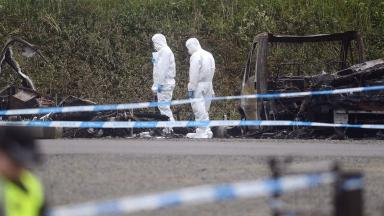 Caravan: Forensic officers investigate fire linked to murder.