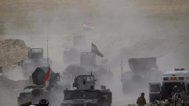 Vehicles of Iraqi security forces move toward Fallujah on June 10.