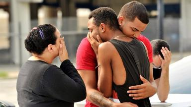 Family and friends embrace after the horrific mass shooting.
