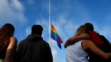 Mourners gather under a LGBT pride flag flying at half-mast.