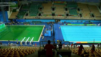 The green diving pool next to the clear blue pool.
