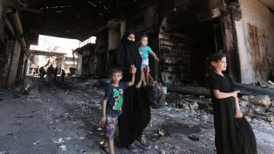 A woman and children flee fighting in the battered city of Aleppo