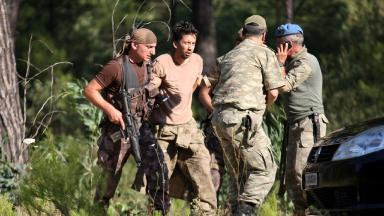 Soldiers detain a member of military personnel suspected of involvement
