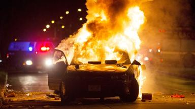 A car burns as a crowd of more than 100 people gathers following the fatal shooting of a man in Milwaukee