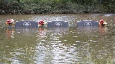 Gravestones are swamped by the floodwater.