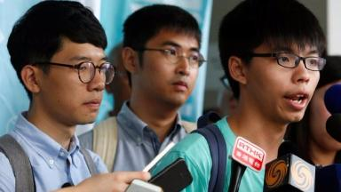 Student leader Joshua Wong speaks outside court beside Alex Chow and Nathan Law