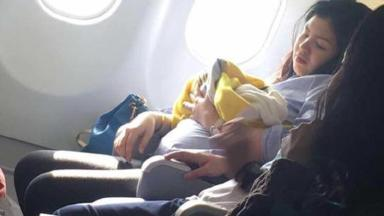 The mother cradles her baby shortly after giving birth on the flight
