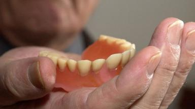 Archive photograph of an elderly man showing artificial dentures.