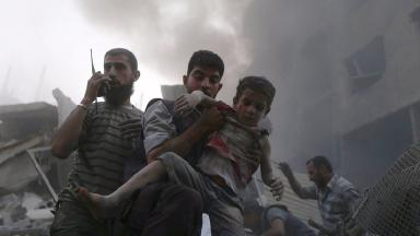 A boy is saved from rubble after heavy shelling by forces loyal to Syrian president Bashar al-Assad.