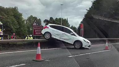 Car ends on crash barrier after M8 collision