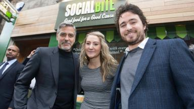 Frame PR handout photo of George Clooney (left) meeting co-founders Alice Thompson and Josh Littlejohn as he visits Social Bite, a cafe in Edinburgh which helps the homeless.