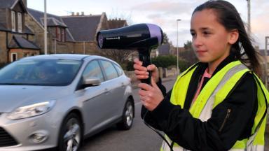 Erin Hepburn, 10, posing with hairdryer as a speed gun in Hopeman, Moray, to deter fast drivers