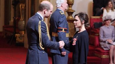 Prince William gives Victoria Beckham her OBE.