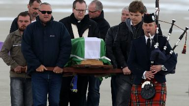 The coffin of Eilidh MacLeod draped in the Barra flag is carried across Traigh Mhor beach at Barra airport after it arrived by chartered plane.