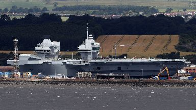 HMS Queen Elizabeth, one of two new aircraft carriers for the Royal Navy sits docked in the sunshine at Rosyth dockyard near Edinburgh ahead of her sea trials which are due to begin soon.