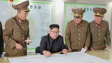 Kim Jong-un was shown examining plans for a strike just off Guam.