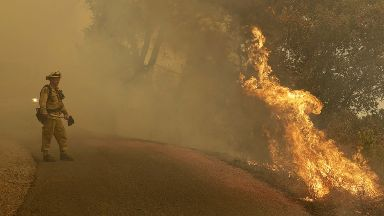 A firefighter monitors flames