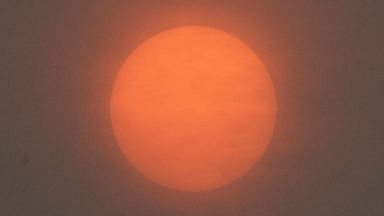 Despite the seemingly thick cloud a brilliant red sun shines through over the river Dart at Dartmouth