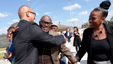 Wilbert Jones huges William Aquino, attorney for Innocence Project New Orleans as he walks free after nearly 50 years in jail.