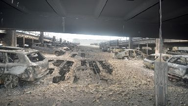 Rows of ruined cars can be seen.