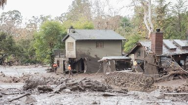 Members of the Heavy Water Search and Rescue Team look for residents along Montecito Creek.