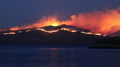 Blaze: Fire crews using boats to asses fire. Black Cuillin of Rum Inner Hebrides