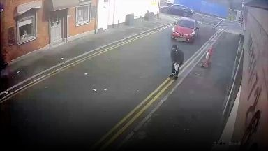 One bungling burglar chases after his money in front of traffic.