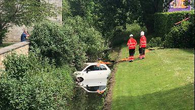 Lyne Burn: Car submerged after ploughing through hedge.