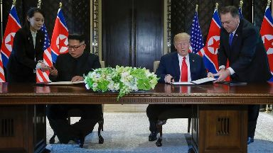 Kim Jong-un and Donald Trump make history as they sign an unspecified document.